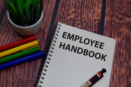 Book about Employee Handbook isolated on wooden table.