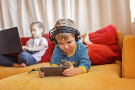 Gadget dependence, digital native generation alpha, kid lying on sofa and using gadgets at home