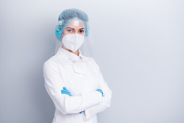Photo of beautiful confident virology doctor lady arms crossed serious professional nurse wear medical coat mask facial plastic protection shield surgical cap isolated grey background