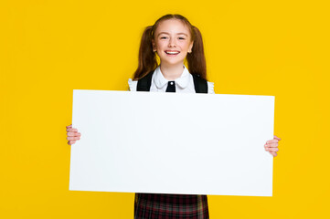 Schoolgirl student pupil holding big empty space white placard banner isolated yellow bright color background and smile
