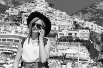 A girl in a sunglasses and a hat stands on the beach in Positano. View of houses and hotels in the background. answers the phone call. Communication and mobile internet network concept. Copy space, BW