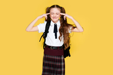 Annoyed schoolgirl on yellow background holding hands on head and close eyes, pupil in uniform and backpack
