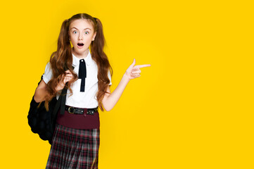 Surprised schoolgirl in uniform and backpack shows something with her finger, student pupil on yellow background, copyspace