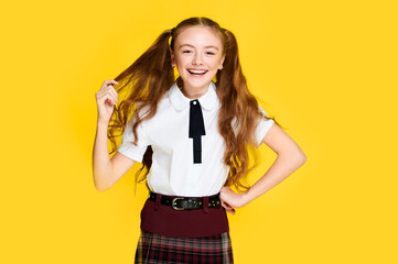 Young happy schoolgirl on yellow isolated background, smiling caucasian pupil, european student, back to school, education learning concept