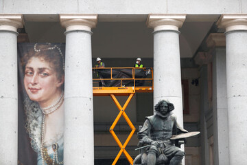 Museum workers remove an old poster from the outside of the Prado museum as it prepares for reopening on June 6th amid the coronavirus disease (COVID-19) outbreak, in Madrid