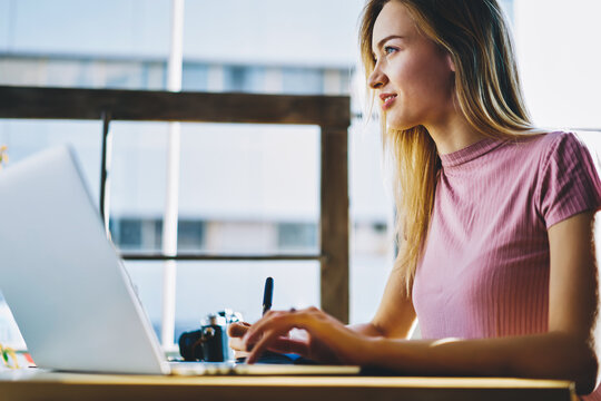 Dreamy female copywriter thinking about completing task earning money online working on freelance near copy space for advertising, side view of creative designer using application on laptop for job