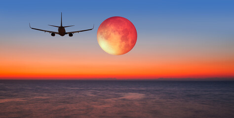 Wall Mural - Passenger airplane flying over sea with lunar eclipse at sunset