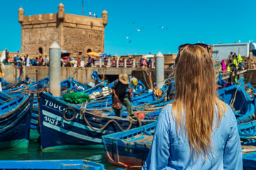 Girl in the port of Essaouira. The famous blue boats.