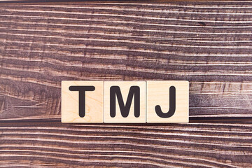 TMJ - acronym from wooden blocks with letters, abbreviation TMJ temporomandibular joint syndrome, TMD Temporomandibular disorder concept.