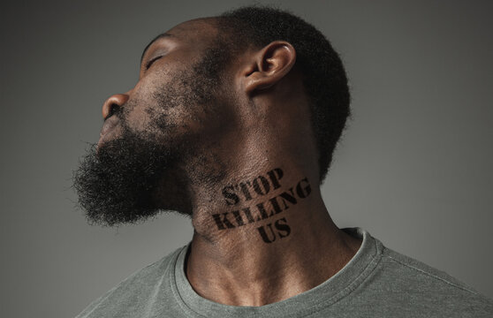 Close up black man tired of racial discrimination has tattooed slogan stop killing us on his neck. Concept of human rights, equality, justice, problem of violence and racism, discrimination.