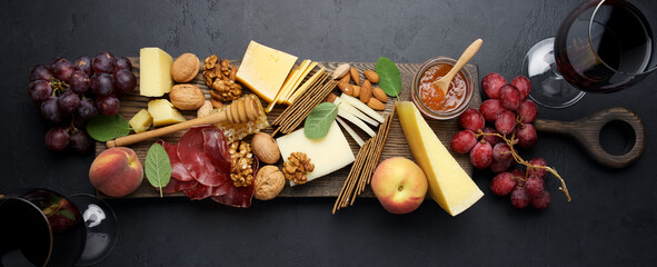 Variety soft and hard cheeses, cold meat bresaola, nuts, grapes, peaches, jam on black background. Cheese plate background. Antipasto Platter