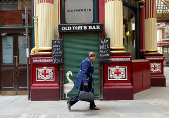 A woman walks past the shuttered exterior door of Old Tom's Bar owned by Young's, in London