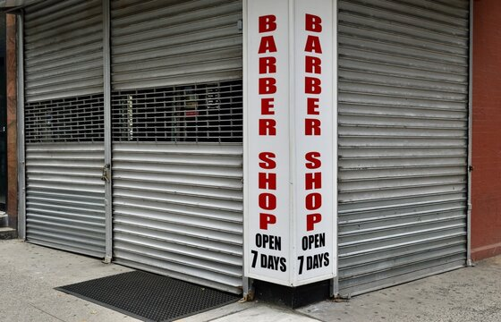 """Closed corner barber shop advertising """"Barber shop open 7 days"""" with metal security barrier gates, June 3, 2020, in New York."""