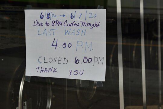 """Handwritten sign in the window of a laundromat reading """"6/2/20 through 6/7/20 - Due to 8PM curfew tonight last wash 4:00PM - closed 6:00PM - thank you"""", June 3, 2020, in New York."""