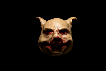 Scary pig mask isolated on black background. Bloody horror mask. Halloween concept.