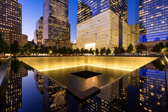 New York City, NY, USA - October 10, 2017: The North Reflecting Pool illuminated at twilight with view of One World Trade Center. Lower Manhattan, 9/11 Memorial & Museum