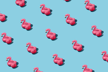 Fashionable pattern with inflatable pink flamingo on a blue background. Summer vacation concept and party poster background.