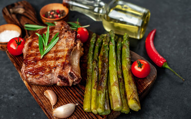 Canvas Prints Grilled beef steak with asparagus with spices on a cutting board on a stone background