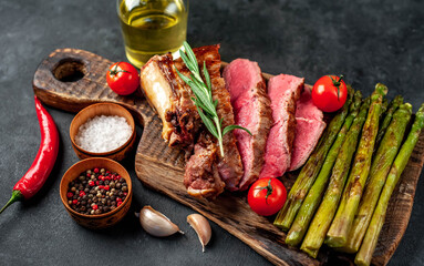 Canvas Prints Grilled beef steak with asparagus and spices on a cutting board on a stone background with copy space for your text