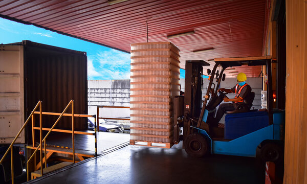 Forklift stuffing-unstuffing pallets of cargo to container on warehouse leveler dock.