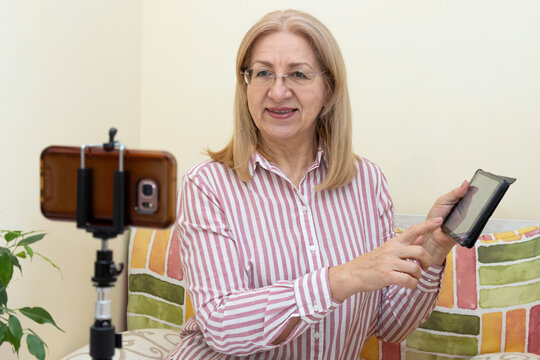 Mature woman conducts online training looking at a smartphone and showing on a digital tablet. Learn over the internet.