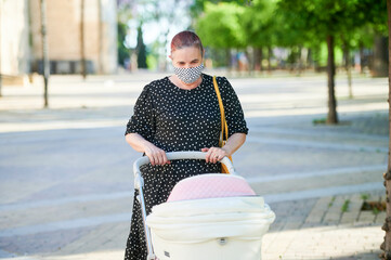 Grandmother with face mask carrying baby carriage