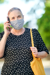 Mature woman wearing face masks while talking on the street with a mobile phone