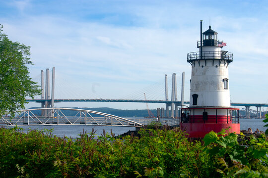 Short, red and white lighthouse situated in Westchester County on the Hudson River with the rebuilt Tappan Zee Bridge in the background.