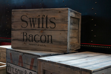 Russia, Saint-Petersburg, 30 May 2018: Old Wooden boxes in the warehouse. Crates for packing Swift Bacon. Pile of stacked. Delivery, cargo, logistic and transportation storage concept.