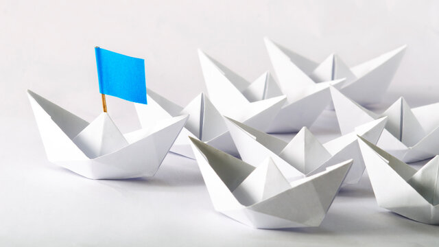To strive against another. Business Competition, Concept using Origami paper boats.