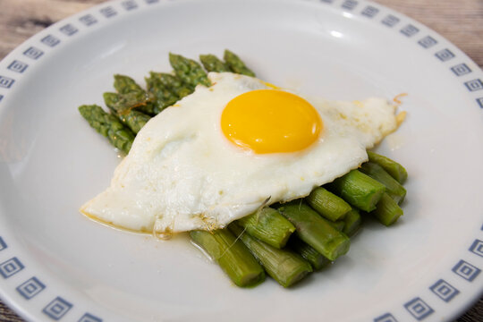 Fried egg with asparagus. Milanese traditional dish.
