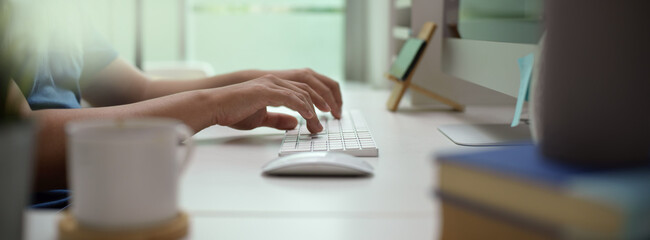 Male entrepreneur typing on computer device on white office desk in modern office room