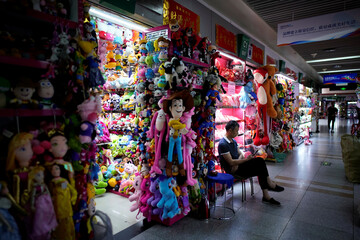 A man sits outside a stall that sells toy products at the Yiwu Wholesale Market following an outbreak of the novel coronavirus disease (COVID-19), in Yiwu