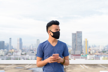 Young multi ethnic man with mask thinking while using phone against view of the city