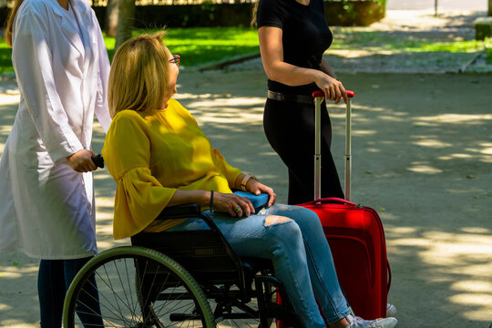 Woman in a wheelchair being pushed while talking with another woman with a suitcase and friendship concept.