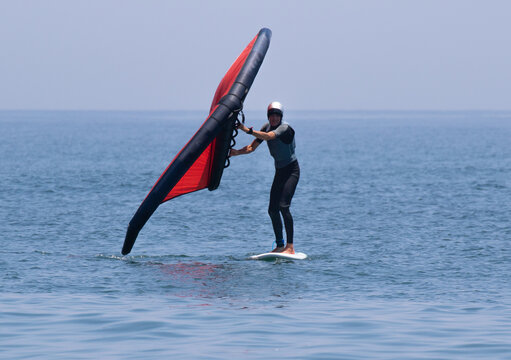 Wing foil in the Pacific Ocean Japan. A man is using an Inflatable wing with a board in the ocean, it is a new sport. Its is red and the ocean blue.