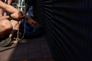 A man holds rosary as he prays near a fence in front of the White House in Washington