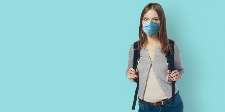 Student woman wearing face mask standing against blue wall with backpack. Safe back to school during pandemic concept. New normal high school education.