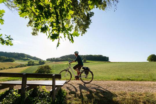 Fahrradtour durch wunderschöne Odenwald Landschaft, Frau fährt mit Elektro Fahrrad im letzten Sonnen Tageslicht.