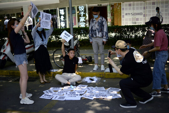 Employees of a recruitment platform promote their company at a stall they set up by a street, near an office complex in Beijing's business district