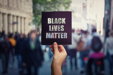 Black Lives Matter, street demonstration. Human hand holds a dark protest banner, against injustice. USA black people rights, social problems concept, racism and inequality. Stop discrimination.