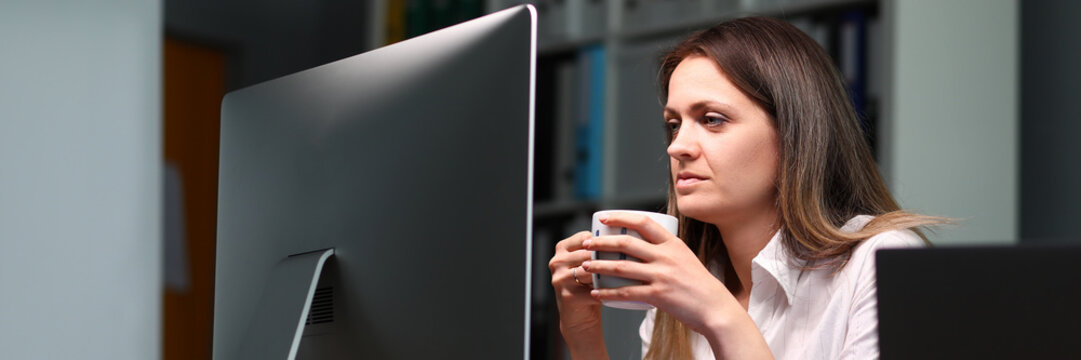 Woman holds mug and looks at monitor intensely