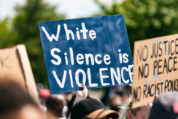 Woman holding White Silence Is Violence sign