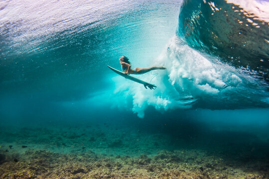 woman in bikini doing duck dive with the surfboard under the waves