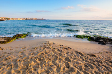 sandy beach with rocks. sunny morning in the resort town. wave brings seaweed on the stones on the shore. beautiful summer vacation landscape with clouds on the blue sky