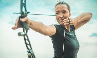 archery, young woman with an arrow in a bow focused on hitting a target