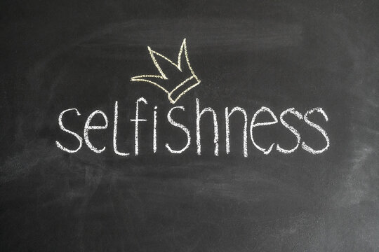 Concept of narcissism and selfishness. The inscription selfishness on a chalk board