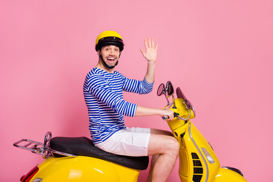 Profile side view of his he nice attractive handsome cheerful cheery glad confident guy driving moped having hi hello good bye isolated over pink pastel color background