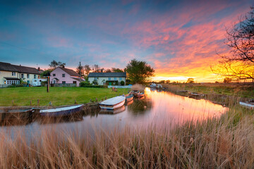 Wall Mural - Stunning sunset over the village green and boats on the river at West Somerton