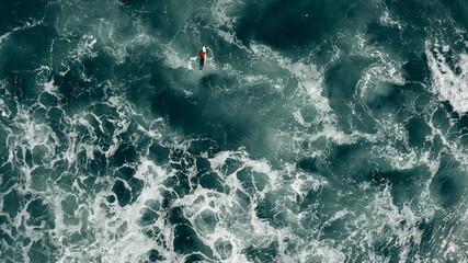 surfer in red paddling in stormy seas
